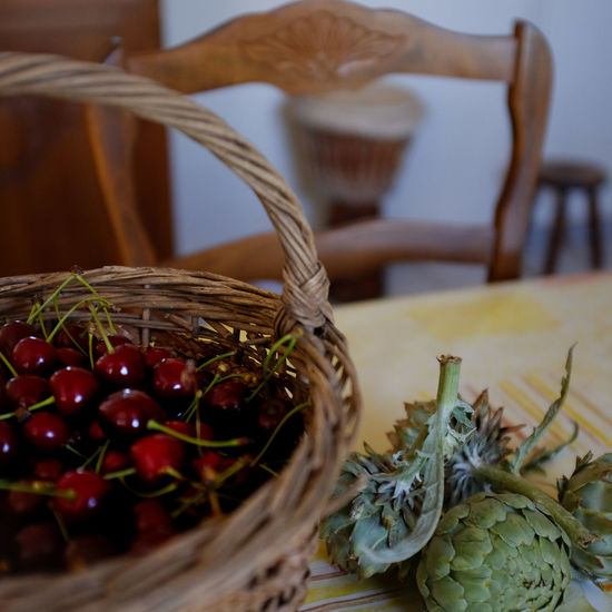 Close-up of cherries in basket by artichoke on table