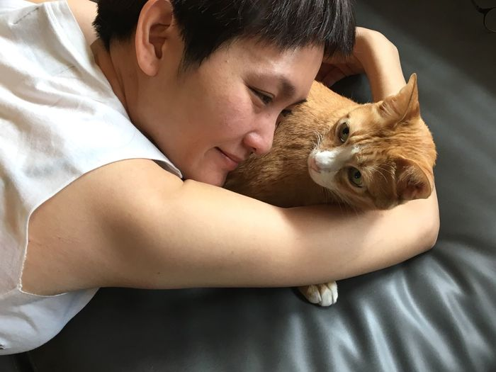 Close-up of smiling woman with cat lying on sofa at home