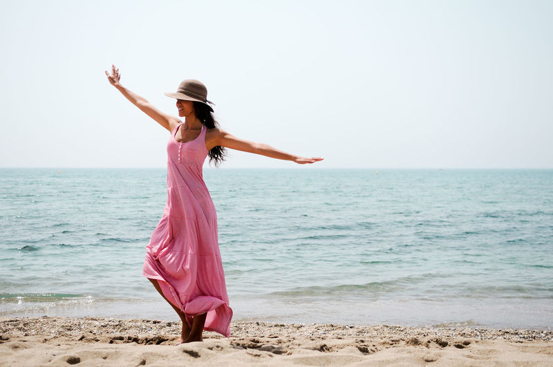 Portrait of a beautiful woman with long pink dress on a tropical beach Beach Beauty In Nature Clothing Dress Fashion Full Length Hairstyle Hat Horizon Horizon Over Water Human Arm Land Leisure Activity Lifestyles One Person Outdoors Pink Color Scenics - Nature Sea Sky Standing Water Young Adult