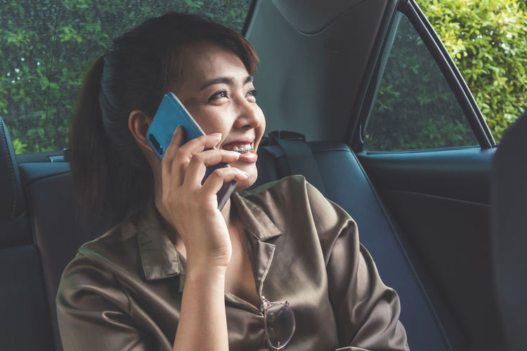 using smart phone in car. Technology Communication One Person Holding Smart Phone Cell Phone  Telephone Line Mobile Phone Close-up Modern Chat Call Hand Woman Device Screen Apple Touch Screen Screen Display Cellular Wireless Technology Internet Online  Transportation Blank White Backgrounds People person E Mail