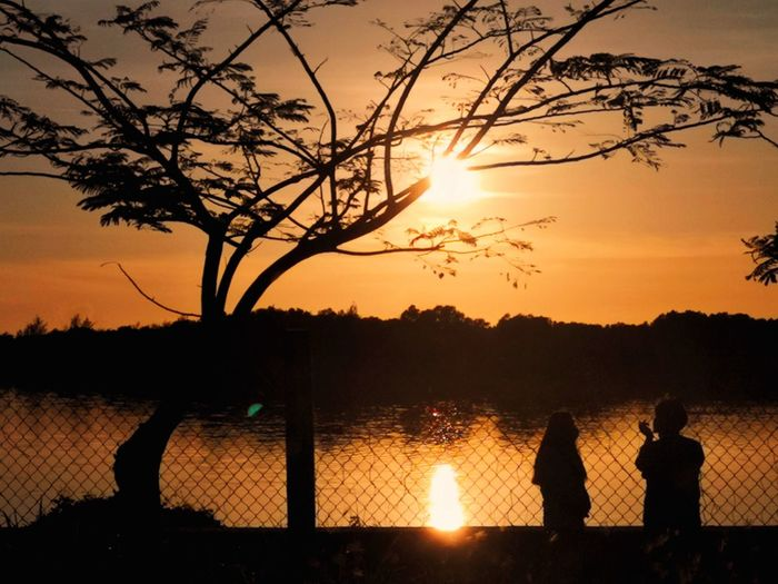 Silhouette people by lake against sky during sunset