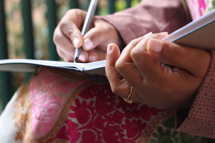 Midsection Of Woman Writing On Book While Sitting Outdoors