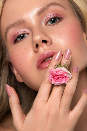 Close-up of beautiful young woman holding flower