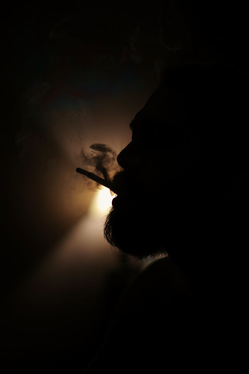 SILHOUETTE MAN SMOKING CIGARETTE AT HOME