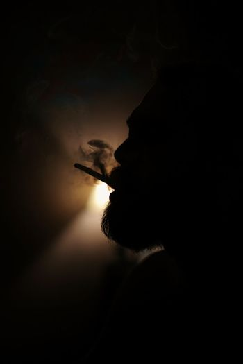 Silhouette man smoking cigarette at night