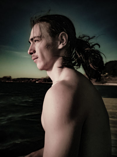 Shirtless young man looking away sitting against sky at dusk