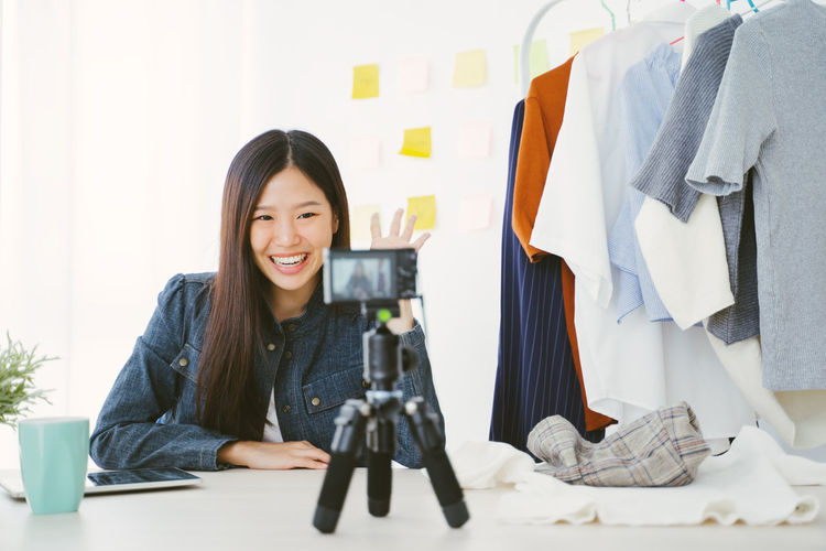 Portrait of young Asian woman recording a video for a woman fashion blogger. Asian  Asian Girl Woman Female Girl Young Women Young Adult Thailand Japanese  Korean Taiwanese Taiwan Beauty Beautiful Beautiful Woman Cute Relaxing Women Lady Portrait Blog Blogger Blogging Youtuber Sale Camera Recording Record Smiling One Person Happiness Front View Table Indoors  Real People Furniture Looking At Camera Casual Clothing Emotion Hair Desk Long Hair Technology Sitting Hairstyle Design Professional Clothing Cloth Clothes
