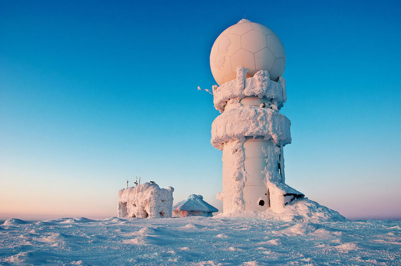 Snow Covered Built Structure Against Clear Blue Sky During Sunset
