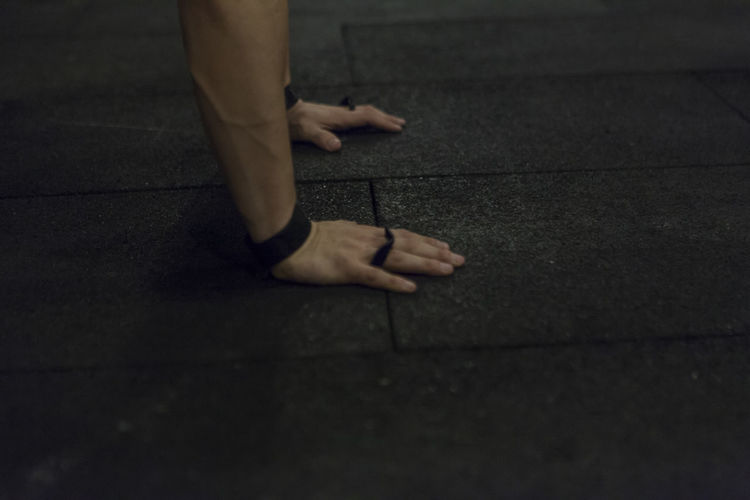 Cropped hands of man doing push-ups on floor at gym