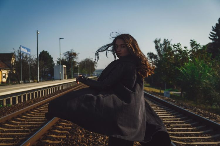 Woman sitting on railroad track against sky