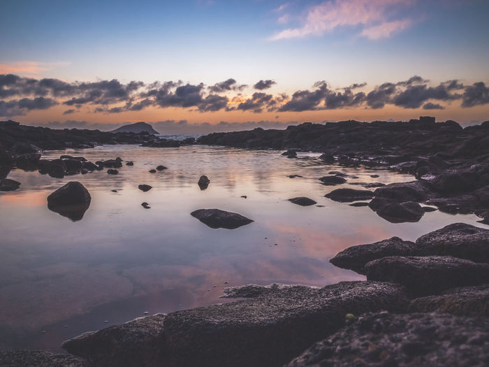 Colors of sunrise seen from a rocky beach with cloud reflections in the sea water