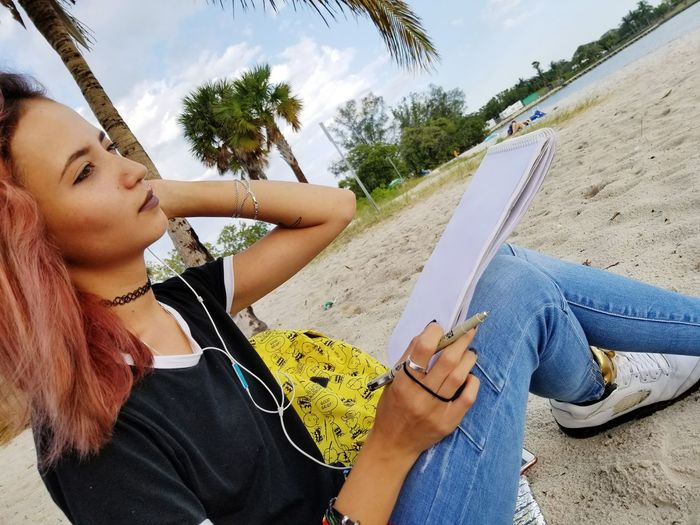 Young Woman With Note Pad Sitting On Sand