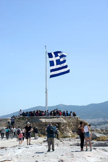 group of tourists among the Acropolis ruins and a greek flag Sky Group Of People Clear Sky Flag Real People Nature Patriotism Land Copy Space Blue Day Crowd People Men Leisure Activity Beach Mountain Lifestyles Outdoors Wind Greek Flag Acropolis, Athens Athens, Greece Archeological Site