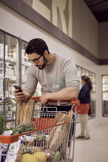 Young man looking at mobile phone in store