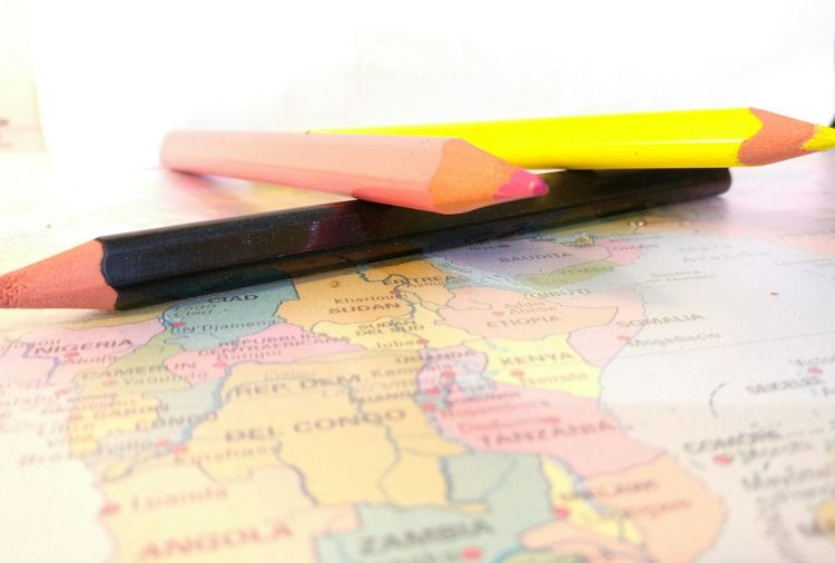 Close-up of colored pencils on world map