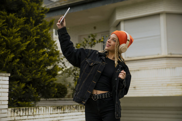 Full length of young woman using mobile phone while standing outdoors