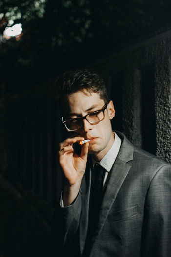 Young man smoking a cigarette EyeEm Best Shots EyeEm Gallery Business Person Businessman Cigarette  Contemplation Eyeglasses  Formalwear Front View Glasses Headshot Holding Illuminated Males  Men One Person Portrait Real People Suit Waist Up Well-dressed Young Adult Young Men