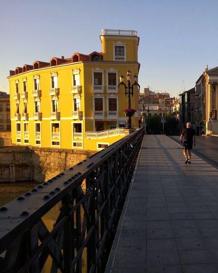 Man walking on bridge in city against clear sky