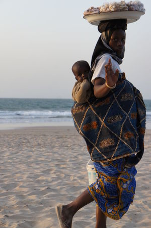 African lady on beach with baby carrying a try of peanuts on her head African African Lady On Beach With Baby Carrying A Try Of Peanuts On Her Head Baby Beach Beauty In Nature Childhood Day Hat Horizon Over Water Lifestyles Nature On Head Outdoors Real People Sand Sea Sky Standing Togetherness Vacations Water Women Young Adult Young Women