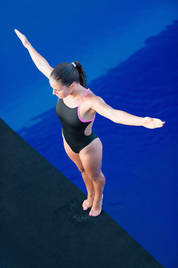 Female Platform Diver Concentrating Swimming Diving Athlete Diving Board Individual Sports Standing Water Sport Woman Arms Outstretched Blue Dive Female High Angle View Muscular Build One Person Outdoors Pool Sport Strength Swimming Pool Vertical Water Young Adult Young Women
