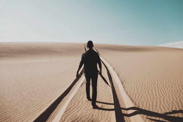Rear view of man walking on desert against sky