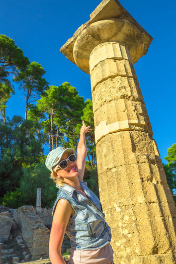 Low angle portrait of woman pointing at old column