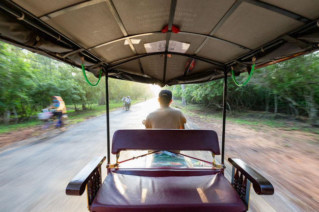 SIEM REAP - JULY 14: An unidentified tuk tuk driver speeds down the road around the Angkor Wat Temple complex on July 14, 2016 in Siem Reap, Cambodia. Angkor Thom Buddha Buddhist Cambodia Hindu Hinduism Khmer Culture Tourist Tourist Attraction  Travel UNESCO World Heritage Site Angkor Wat Apsara Buddhism Cambodian Khmer Khmer Empire Khmer Temple Sculpture Southeast Asia Temple Tour Tourism Tourist Destination Tuk Tuk Unesco