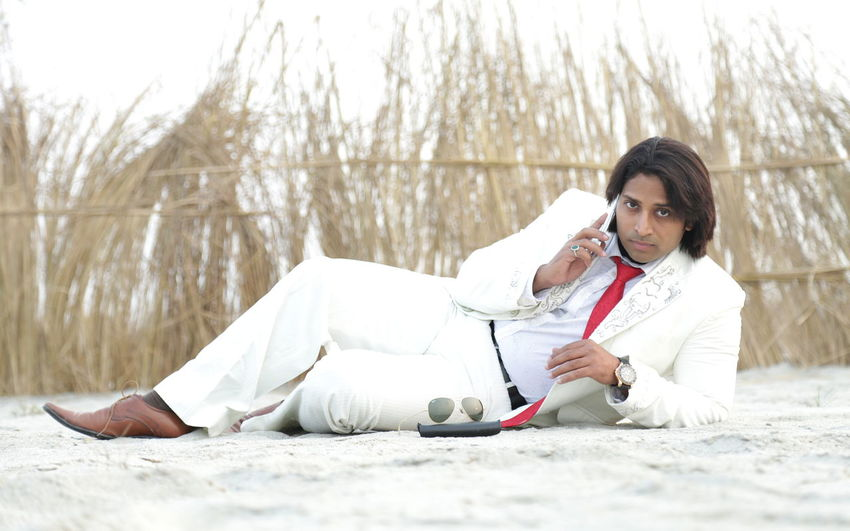 Man in white suit using phone on beach
