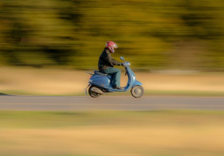 Side view of man riding motor scooter on road