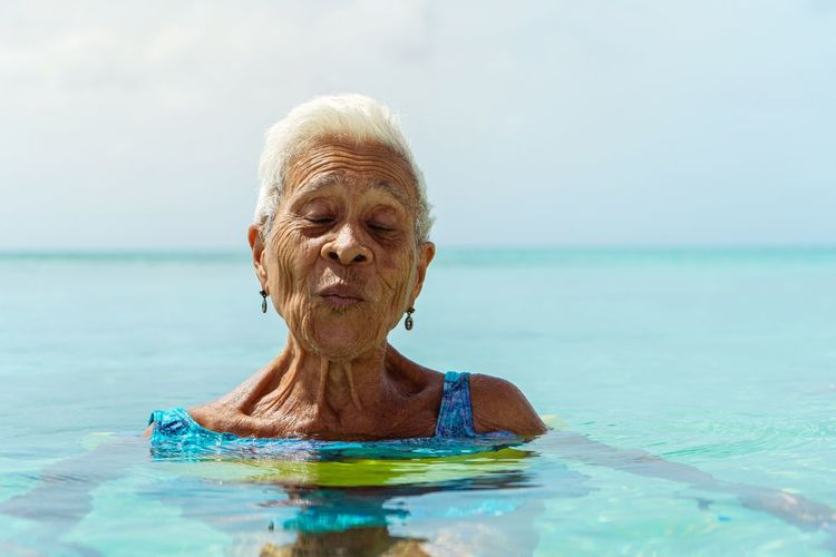 Woman in front of swimming pool against sea