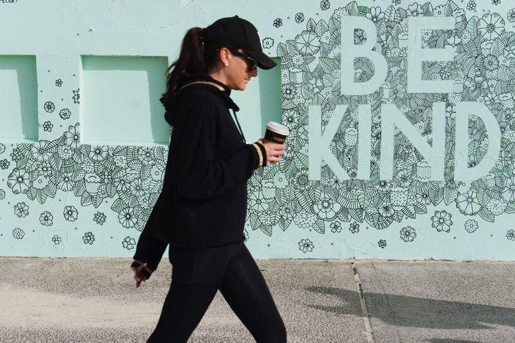 Woman walking with take away coffee across the graffiti wall saying be kind Communication One Person Standing Business Wireless Technology Young Adult Real People Full Length Day Outdoors People Adult Adults Only Coffee Take Away Coffee Morning Walk