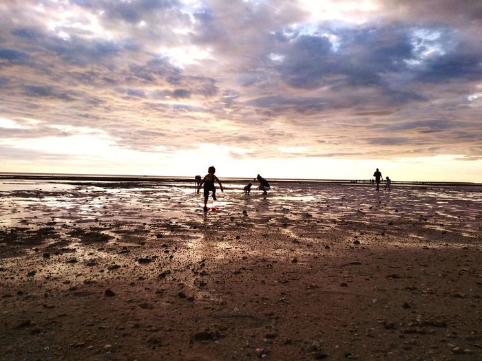 People On Shore At Beach Against Cloudy Sky During Sunset