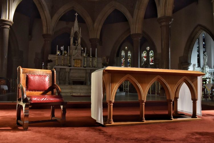 Empty chair and table at altar in church