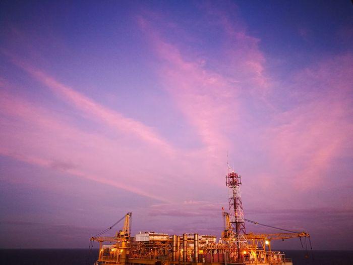 Illuminated offshore platform against sky at sunset
