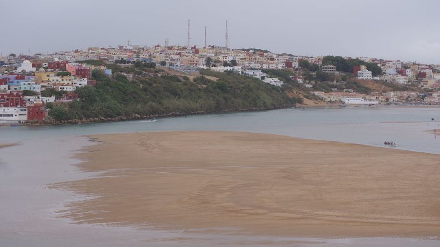 Distant view of houses in front of sea against sky