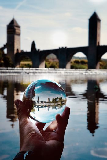 Cropped image of hand holding crystal ball against river in city