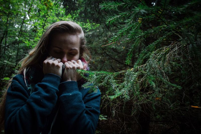 Young Woman With Eyes Closed Standing By Pine Tree In Forest