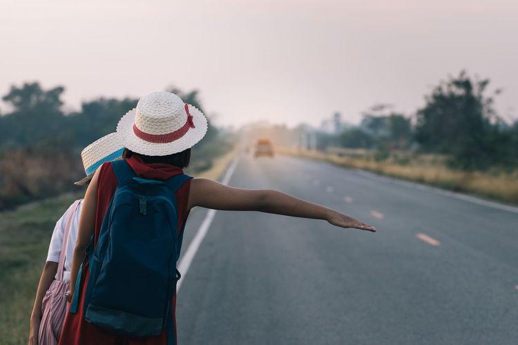 Women Hitchhiking On Road