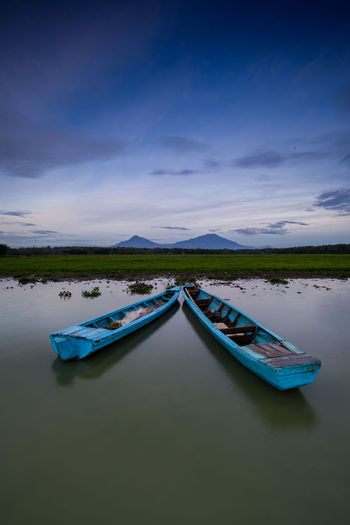 Rowboats moored in river against sky at dusk