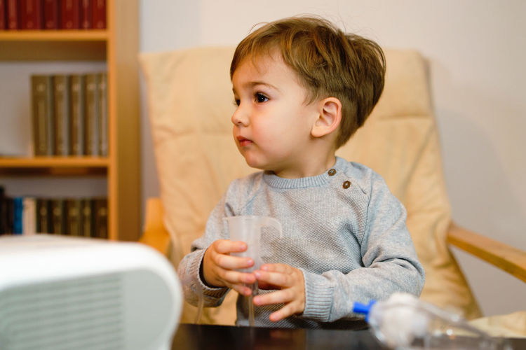 Close-up of cute boy using asthma inhaler at home