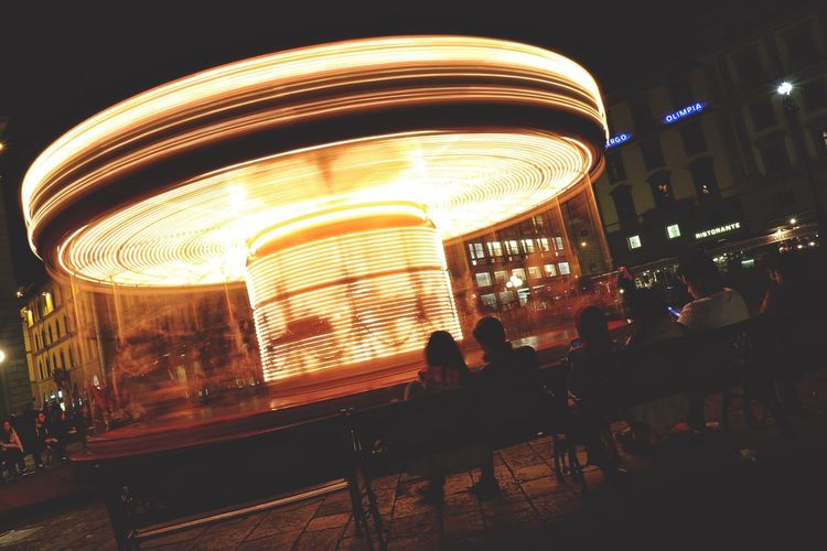 People in illuminated amusement park at night