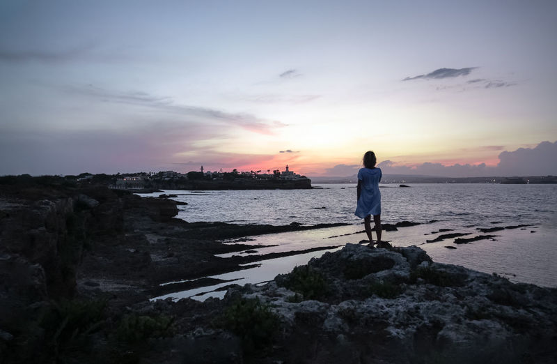 Silhouette woman standing on rock by sea against sky during sunset