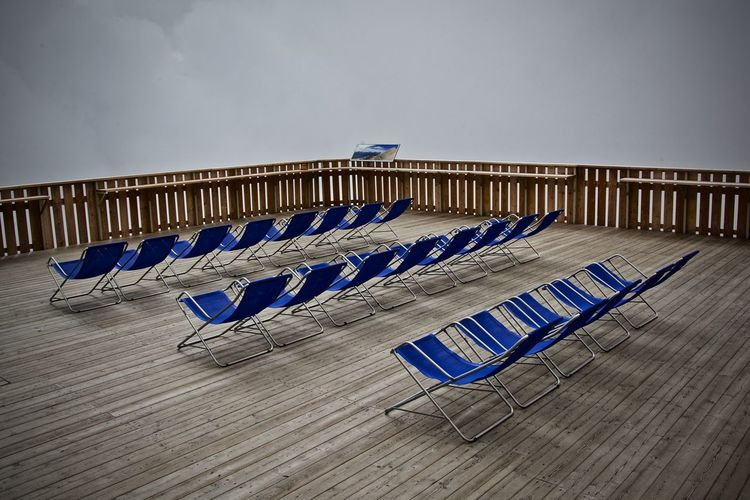 Empty chairs on floor against blue sky