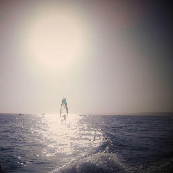 People on sea against clear sky