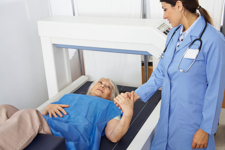 Doctor consoling patient lying at mri scanner