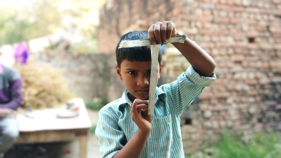 Portrait of boy holding old plastic while standing in village