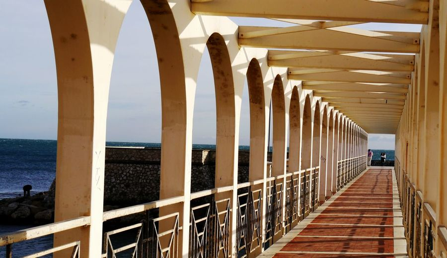 Elevated Walkway By Sea On Sunny Day