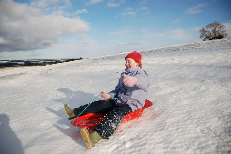 Smiling Girl Sledging On Snow Against Sky