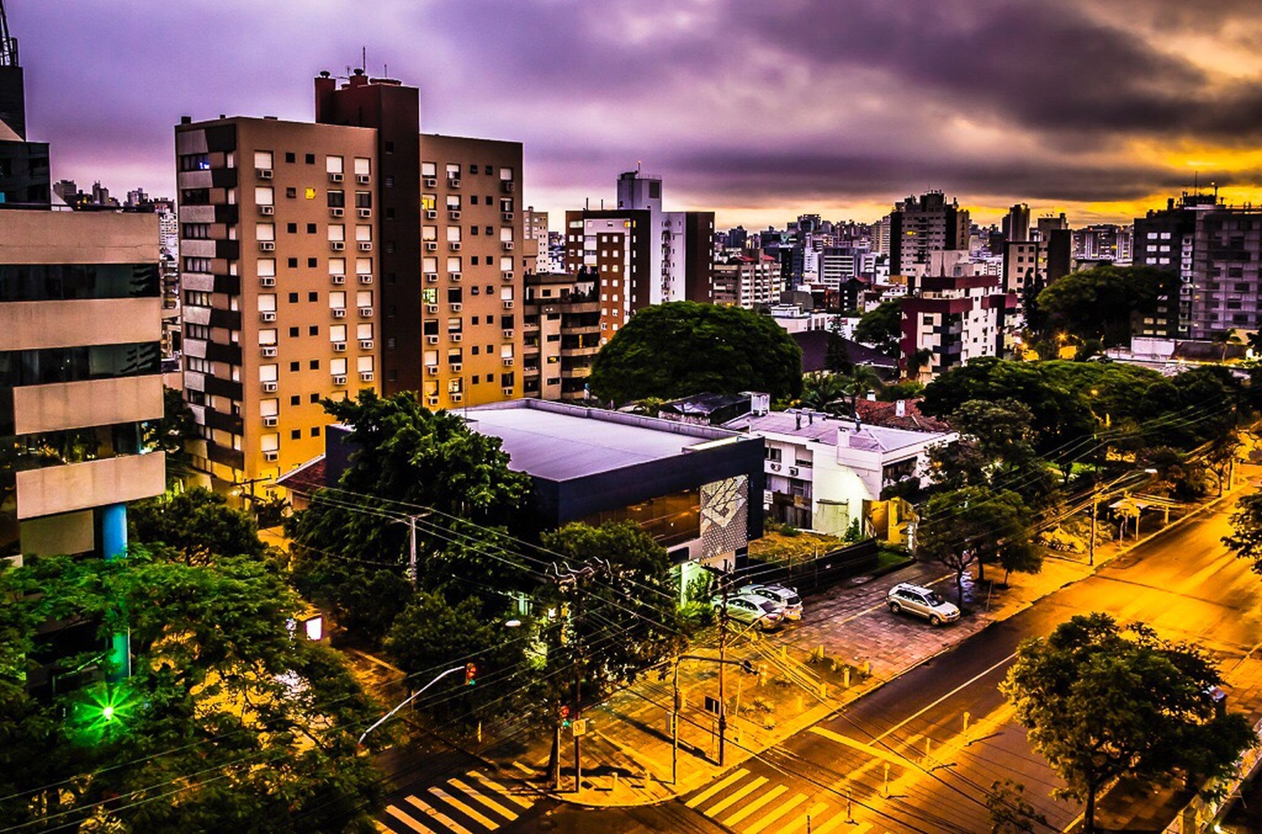 building exterior, city, architecture, built structure, tree, skyscraper, modern, dusk, cityscape, growth, business finance and industry, tower, sky, outdoors, city life, no people, sunset, apartment, illuminated, urban skyline, dramatic sky, cloud - sky, night, building story
