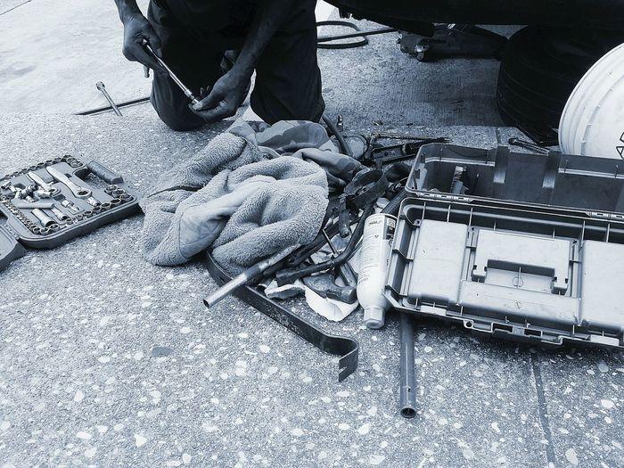 High angle view of mechanic kneeling on floor with tools